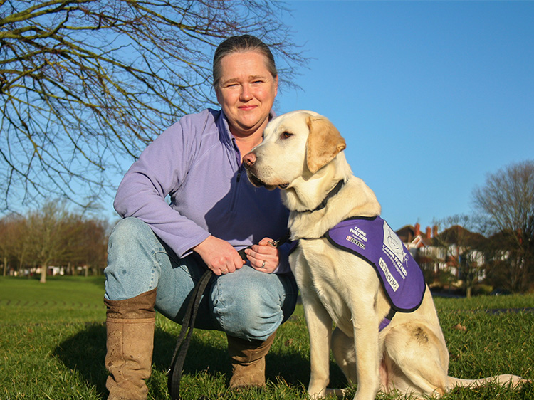 Ruth Breading, a puppy socialiser for Canine Partners with a puppy in training