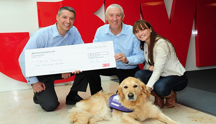 3M staff presenting cheque for £1,000 to Head of Donor Development Cat Harvey and meet and greet dog Jenson
