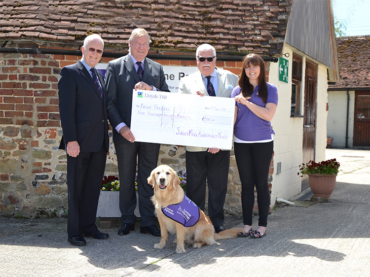 Sussex Benevolent Fund cheque presentation with staff and meet and greet dog Jenson