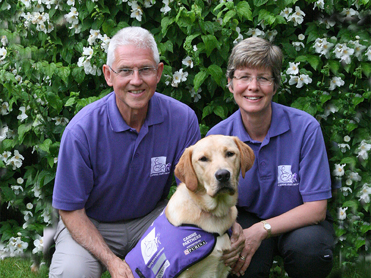 Two puppy parents posing with a Canine Partner in training. Puppy parents socialise the puppies before they start advanced training