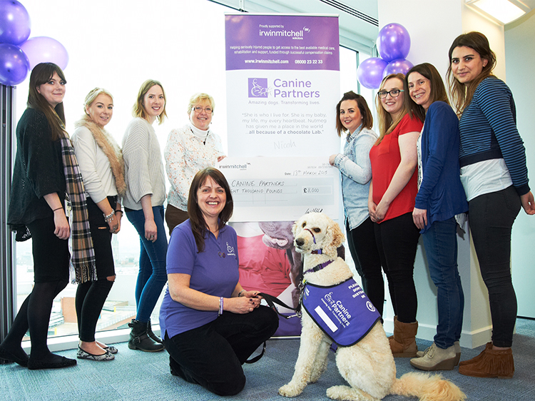 Canine Partners and Irwin Mitchell staff holding giant cheque as a major gift donation