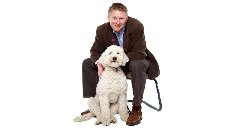 Canine Partners CEO Andy Cook sat on chair alongside white poodle cross dog