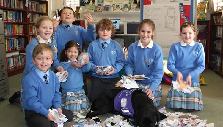 A group of school pupils with a Canine Partners demonstration dog posing with lots of stamps to promote the Charity's stamp appeal