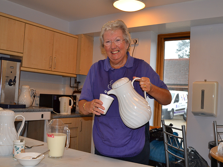 Information session helper volunteer Barbara pouring a cup of coffee