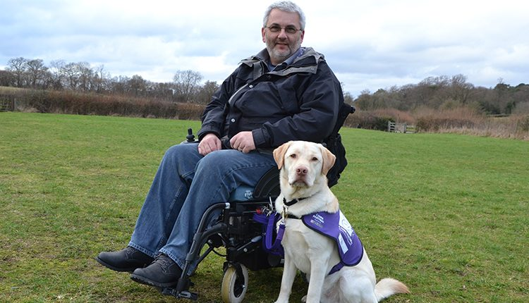 Martin and assistance dog Keith on South Downs field