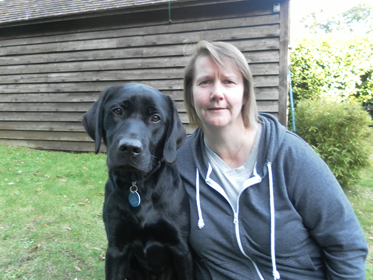 Foster parent for dogs Val posing with black labrador.
