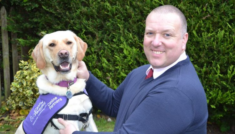 Jonathan Giemza-Pipe and assistance dog Toby on his lap