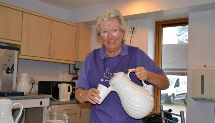Canine Partners volunteer pouring a hot drink from a white jug