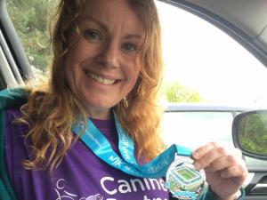 Canine Partners fundraiser Sam Foster holding Milton Keynes marathon medal