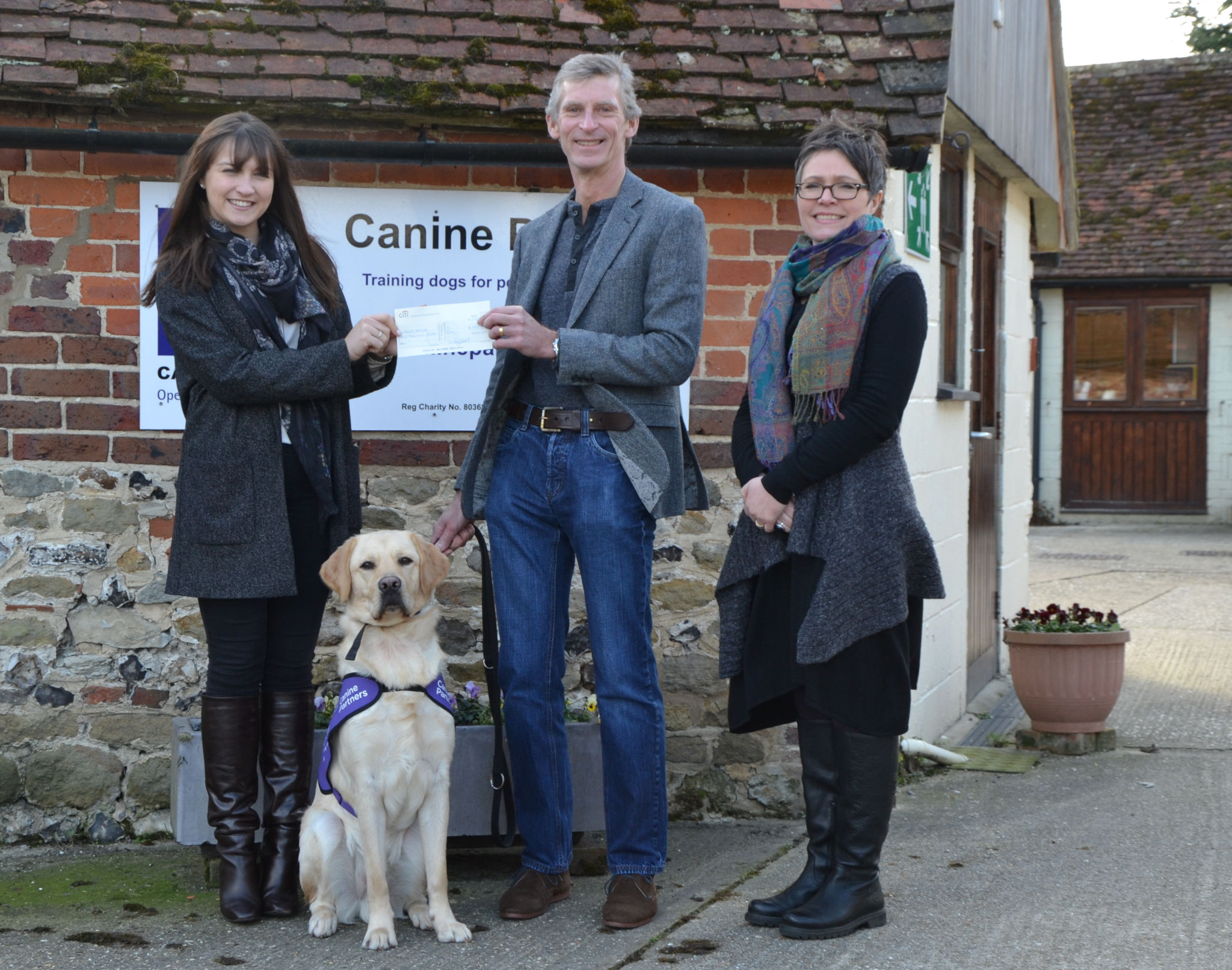 Members of the Income Generation Team and a dog in training at Canine Partners receiving a cheque from a Charitable Trust